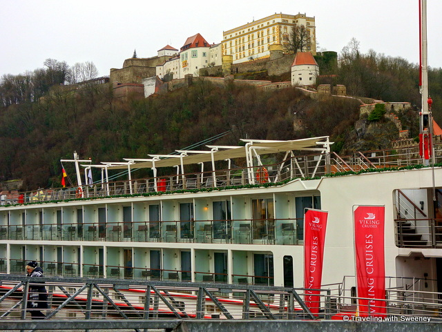 Daytime photo of the Viking Gullveig with Veste Oberhaus on a hilltop above at port in Passau, Germany
