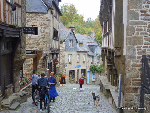 Locals going about their day on Rue du Jerzual in Dinan, France