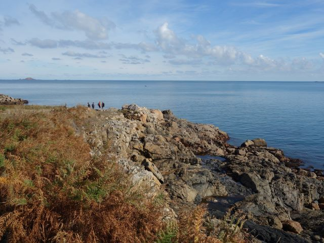 Visitors walking atop the rock formations of Perros-Guirec on Brittany's Pink Granite Coast