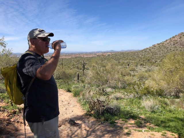 Taking a water break while hiking a trail in the McDowell Sonoran Preserver in Scottsdale, Arizona