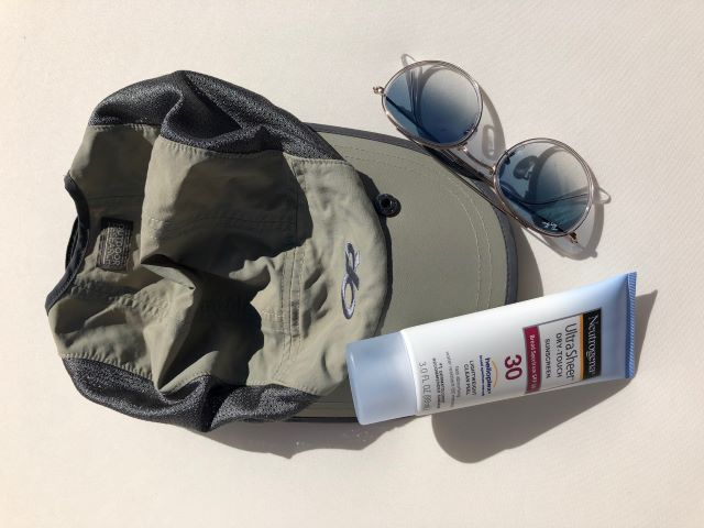 Preparing for a hike: hat, sunglasses and sunscreen