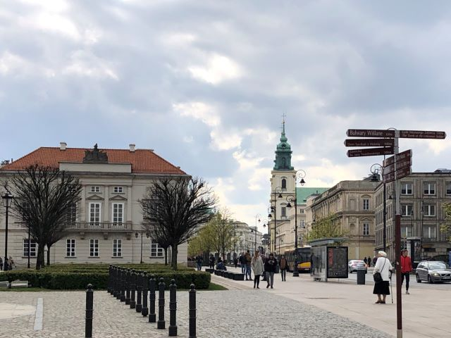 Scene of pedestrians on a city street in Warsaw, Poland and Holy Cross Church on the right