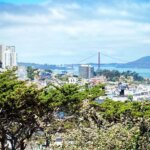 View of Golden Gate Bridge beyond the rooftops of San Francisco seen from the base of Coit Tower