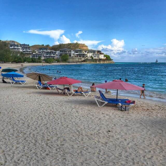 Umbrellas on the white sand of Ffryes Beach in Antigua